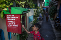 Ihsan, 11, looks for something to read in one of five book-sharing boxes that have been installed along the narrow alleys of the Jatipulo literacy kampung in West Jakarta. JP/Afriadi Hikmal