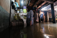 Life goes on: A local resident, Nurhayati, cooks in her flooded kitchen in Satria Raya Grogol, West Jakarta, on Tuesday. JP/Donny Fernando