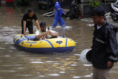 Pleasure cruise: A man takes a selfie as he is pushed in a rubber boat in an inundated part of Jl. Kemang Raya in South Jakarta on Tuesday. JP/Wendra Ajistyatama