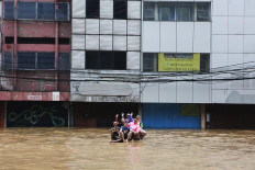 Chilling out: A number of people pose amid the floodwaters on Jl. Gunung Sahari, Central Jakarta, on Tuesday. JP/Seto Wardhana
