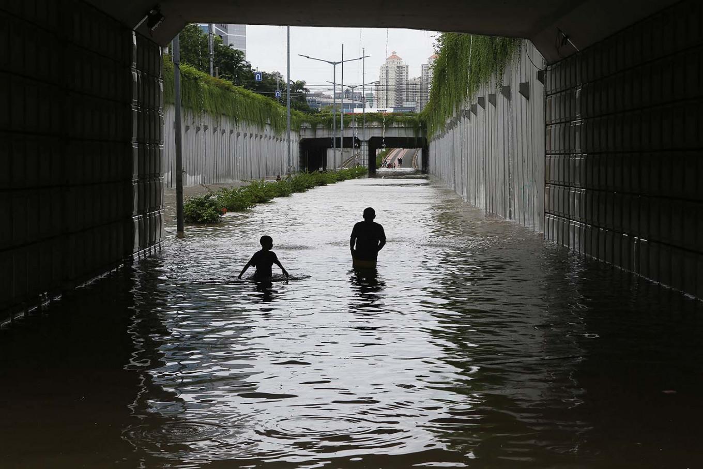 Urban river: Kids play under the inundated Kemayoran underpass in Gunung Sahari, Central Jakarta, on Tuesday. JP/Seto Wardhana