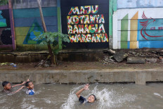 Have fun where you can: Children swim in a flooded area in Bukit Duri, Central Jakarta, on Tuesday. The area was flooded because of the poor condition of the local drainage system. JP/Dhoni Setiawan