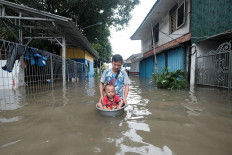 Boy in a tub: A man floats his son in a plastic basin while passing through an inundated part of Jl.Raya Grogol in West Jakarta on Tuesday. JP/Donny Fernando