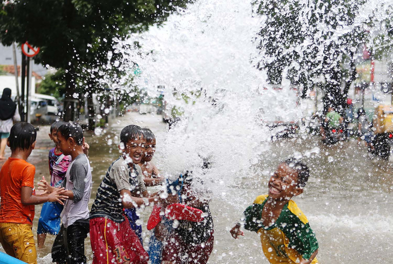 Making a splash: Children play in flood water on Jl. Gunung Sahari in Central Jakarta on Tuesday. JP/Seto Wardhana
