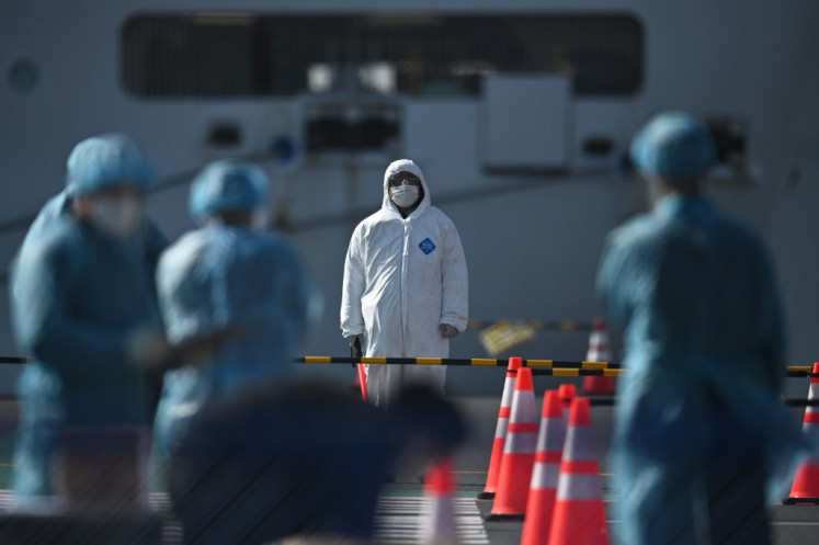 Workers in protective clothes stand before passengers disembarking off the Diamond Princess cruise ship, in quarantine due to fears of new COVID-19 coronavirus, at Daikoku pier cruise terminal in Yokohama on February 21, 2020.