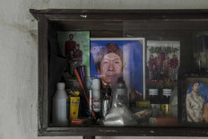 A cupboard displays a photograph (center) of Puspita's celebrated father, Dalang Priyo Widodo. He is the one who first taught Puspita the traditional performing art of wayang.  JP/Irene Barlian