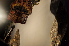 """Dalang (puppet master) Dwi Puspita skillfully wields a character in a wayang kulit (shadow puppet) performance. The term wayang is Javanese and means """"shadow"""" or """"imagination."""" JP/Irene Barlian"""