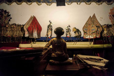"""Dalang Dwi Puspita enjoys a quiet moment behind the screen of a wayang show before opening """"Punakawan"""". """"Punakawan"""", which follows a tragic event in the narrative, presents the four popular comic characters of Semar, Petruk, Bagong and Gareng, and is one of the most anticipated acts in a wayang show. JP/Irene Barlian"""