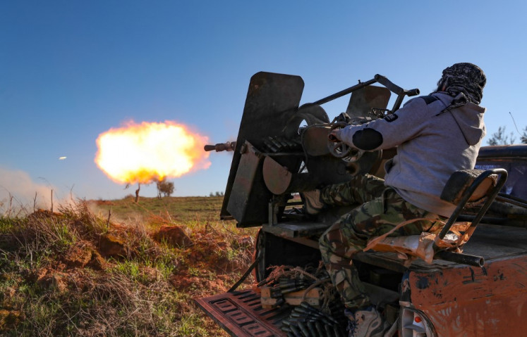 A Turkey-backed Syrian fighter fires a truck-mounted gun toward the town of Saraqeb from the outskits of the villages of Afis and Salihiyah situated near the regime-controlled town, in the eastern part of the Idlib province in northwestern Syria, on February 26, 2020.