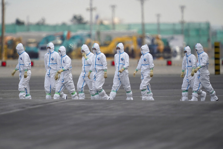 Workers in protective gear walk near the Diamond Princess cruise ship, operated by Carnival Corp., docked in Yokohama, Japan, on Friday, Feb. 7, 2020. Japan confirmed 41 more cases of the new coronavirus aboard the quarantined cruise ship, and denied entry to another vessel as it sought to control the spread of the deadly infection, with thousands now stranded on stricken luxury liners.