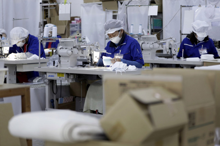An employee, center, uses a sewing machine while making {reusable-type} face masks at the Clever Co. factory in Toyohashi, Aichi Prefecture, Japan, on Friday, Jan. 31, 2020.