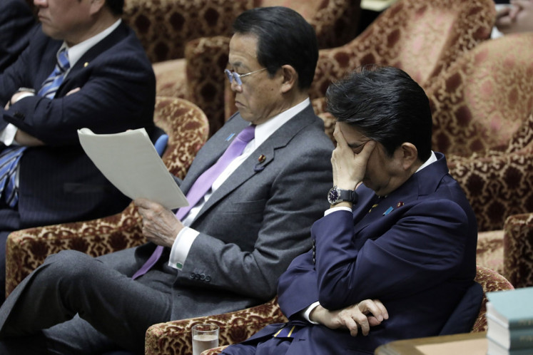Shinzo Abe, Japan's prime minister, right, covers his face next to Taro Aso, deputy prime minister and finance minister, while attending a budget committee session at the lower house of parliament in Tokyo, Japan, on Wednesday, Feb. 26, 2020.