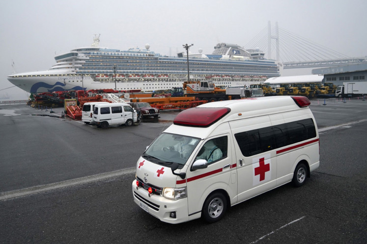 An ambulance travels away from the Diamond Princess cruise ship, operated by Carnival Corp., docked in Yokohama, Japan, on Sunday, Feb. 16, 2020. Aircraft chartered by the U.S. State Department are to arrive Sunday in Japan to evacuate about 400 citizens from the Diamond Princess.