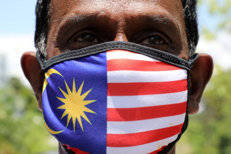 A supporter of People's Justice Party wearing Malaysia's flag mask pose for a picture outside National Palace, Kuala Lumpur, Malaysia. February 26, 2020.
