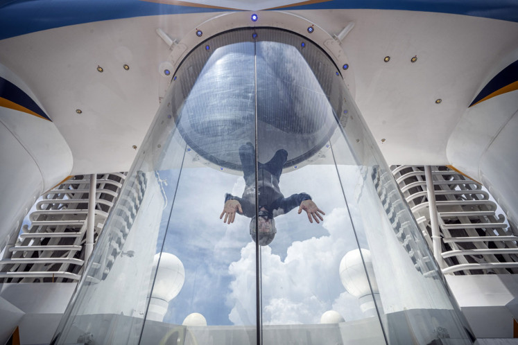 A performer demonstrates on a iFly Holdings LLC body flying tunnel on The Spectrum of the Seas cruise ship, operated by Royal Caribbean Cruises Ltd.'s cruise line brand Royal Caribbean International (RCI), as the ship sits berthed at the Marina Bay Cruise Center in Singapore, on Tuesday, May 21, 2019. For the better part of a decade, wealthy Chinese tourists have been on a feeding frenzy for luxury brands, casinos and cruise lines. As a result, China became the world's biggest spender in international tourism in 2012, according to data from the World Tourism Organization, a United Nations agency.