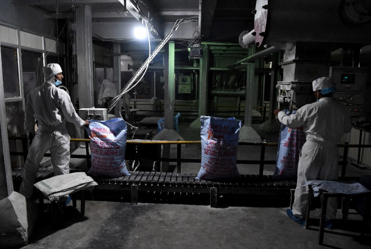 In this photograph taken on January 23, 2019, Indian workers pack processed sugar at the Triveni sugar refining factory in Sabitgarh village, in Bulandshahr district in the northern state of Uttar Pradesh.