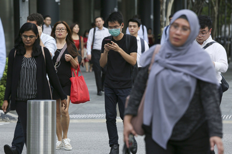 A man wearing a protective mask looks at his mobile phone as he walks through the Marina Bay business district in Singapore, on Wednesday, Feb. 12, 2020.