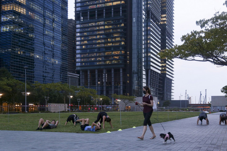 A pedestrian walking a dog passes a group of people work out in a field at the Marina Bay financial district in Singapore, on Wednesday, Feb. 12, 2020.