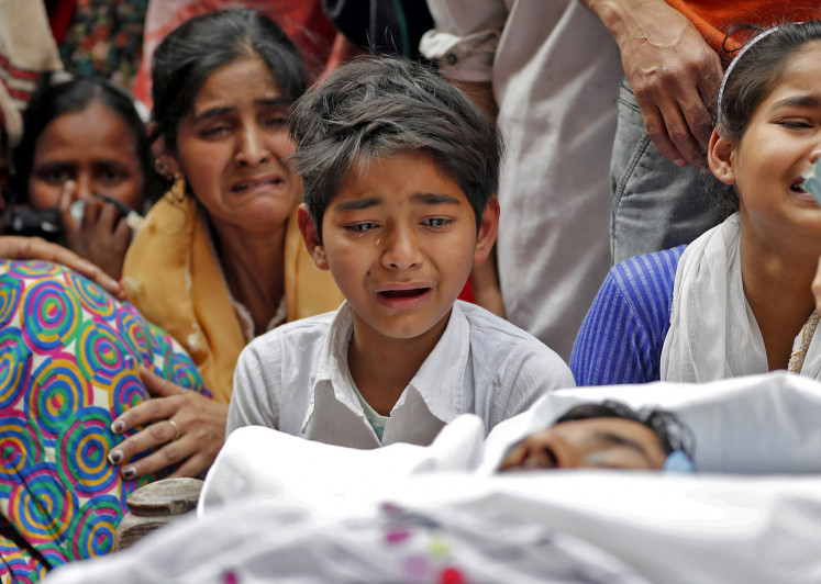 People mourn next to the body of Muddasir Khan, who was wounded on Tuesday in a clash between people demonstrating for and against a new citizenship law, after he succumbed to his injuries, in a riot affected area in New Delhi, India, February 27, 2020.