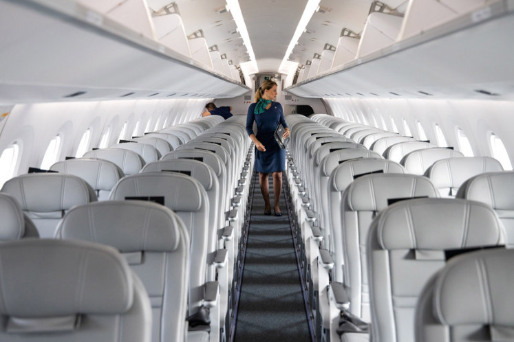 A cabin crew inspects inside an Embraer SA 195-E2 aircraft at the Singapore Airshow held at the Changi Exhibition Centre in Singapore, on Tuesday, Feb. 11, 2020.