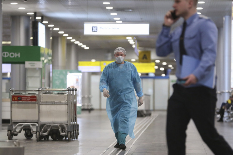 A health worker wearing a protective suit and face mask walks through the arrival area at Sheremetyevo International Airport OAO in Moscow, Russia, on Wednesay, Feb. 26, 2020. The number of coronovirus cases continues to climb, with the global death toll nearing 3,000.
