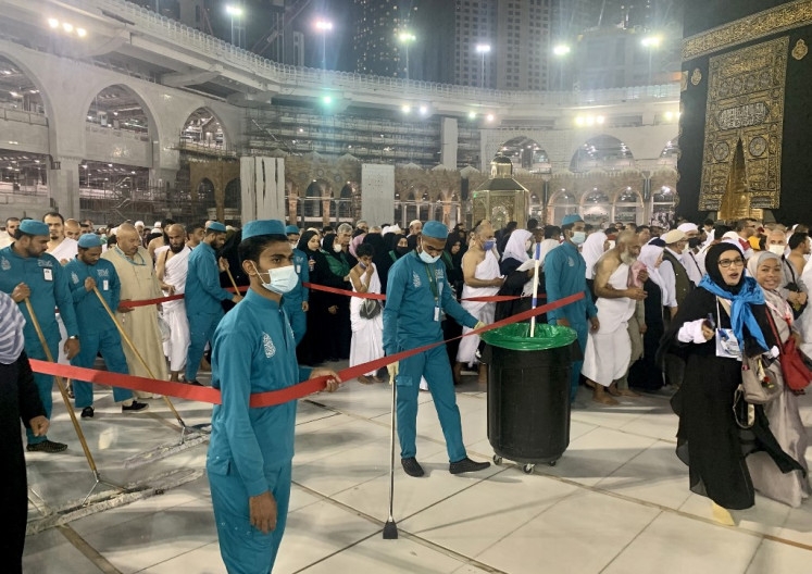 Sanitary workers wearing protective face masks continue to clean the sahn (mosque courtyard) surrounding the Kaaba, Islam's holiest shrine, as Muslim worshippers pray at the Grand Mosque complex in Saudi Arabia's holy city of Mecca on February 27, 2020.