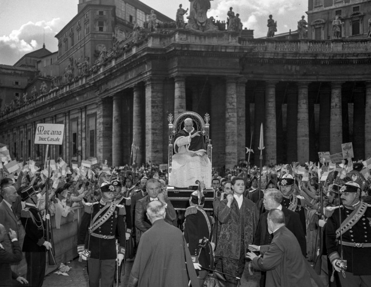 This undated photo provided by Italian news agency Ansa shows Pope Pius XII (carried at C on chair) blessing young people belonging to the Gioventu Catholic Action at St. Peter's Square in the Vatican.