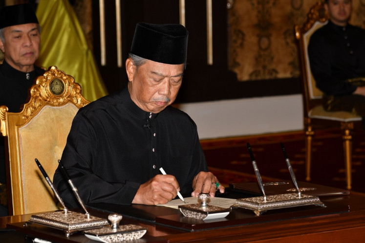 This handout from Malaysia's Department of Information taken and released on March 1, 2020 shows Malaysia's Prime Minister Muhyiddin Yassin signing documents after taking the oath as the country's new leader at the National Palace in Kuala Lumpur.