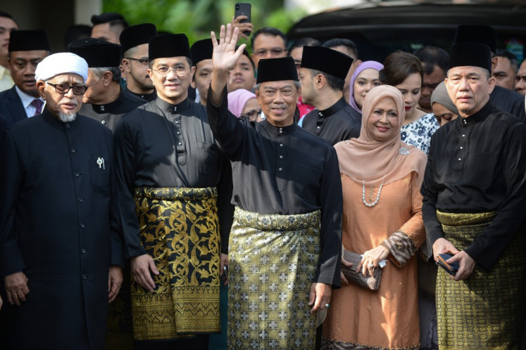 This handout from Malaysia's Department of Information taken and released on March 1, 2020 shows Malaysia's incoming Prime Minister Muhyiddin Yassin (C) waving outside his residence in Kuala Lumpur before his swearing-in ceremony as the country's new leader.