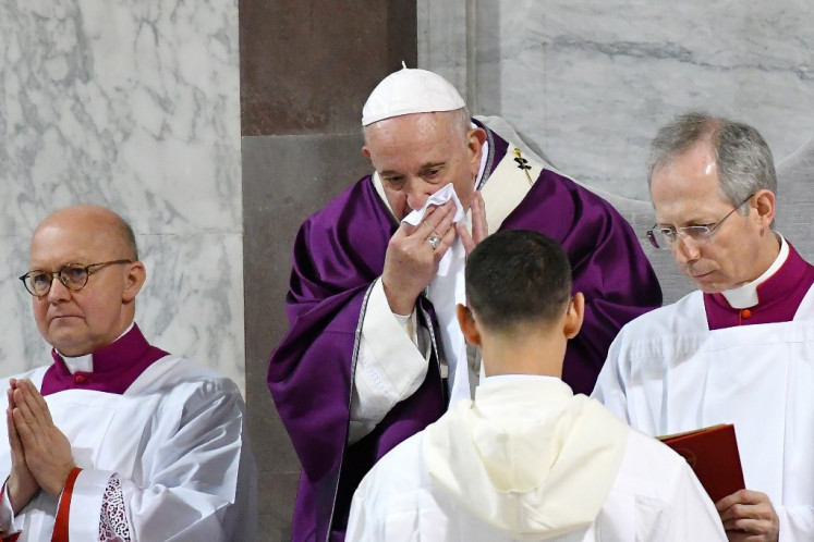 Pope Francis wipes his nose during the Ash Wednesday mass which opens Lent, the forty-day period of abstinence and deprivation for Christians before Holy Week and Easter, on February 26, 2020, at the Santa Sabina church in Rome. - Pope Francis postponed his official appointments on February 28 and was working from home, the Vatican said, a day after cancelling a scheduled appearance at mass because of