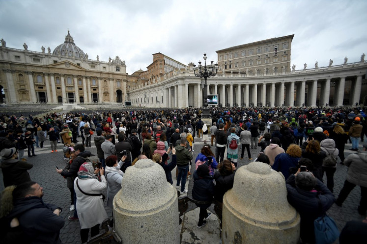 Faithfuls listen to Pope Francis' speech as he delivers the Sunday Angelus prayer from his studio window overlooking St. Peter's Square, at the Vatican on March 01, 2020.