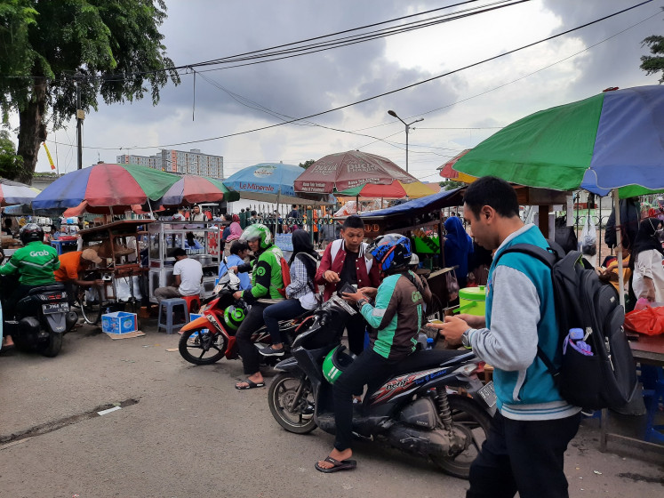 App-based ojek (motorcycle taxi) drivers drop off customers in front of the Tanah Abang railway station's gate in Central Jakarta.