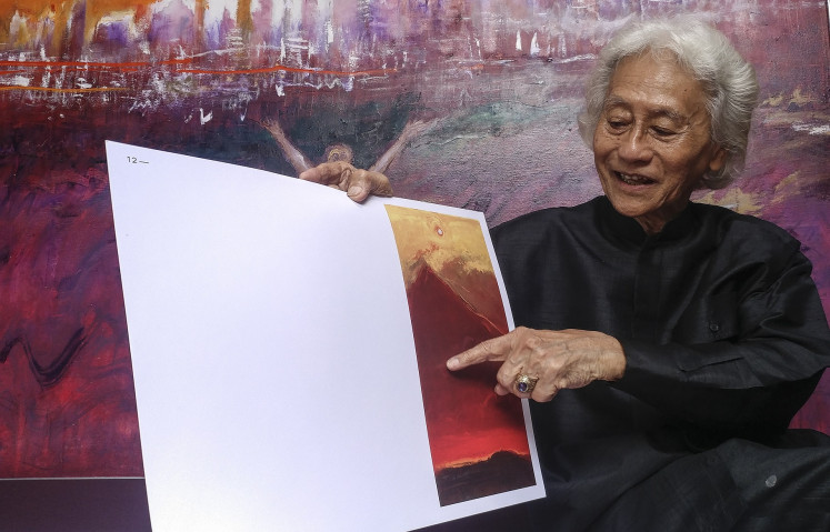 How it came to be: Srihadi explains one of his paintings called 'Mt. Merapi – The Powerful Nature' at his studio in Bandung, West Java.