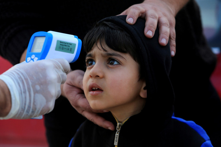 A member of the medical team checks the temperature of a child, following the coronavirus outbreak, at a checkpoint on the outskirts of Duhok, Iraq March 2, 2020.