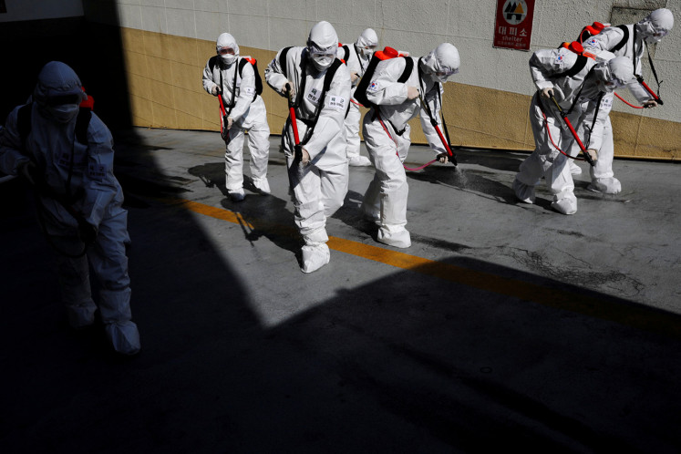 South Korean soldiers wearing protective gear sanitize a street in front of the city hall after the rapid rise in confirmed cases of the novel coronavirus disease of (COVID-19) in Daegu, southeast of the capital Seoul, South Korea, March 2, 2020.
