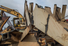 Marine mound: A worker moves the ruins of a dismantled ship using heavy equipment.. JP/Afriadi Hikmal