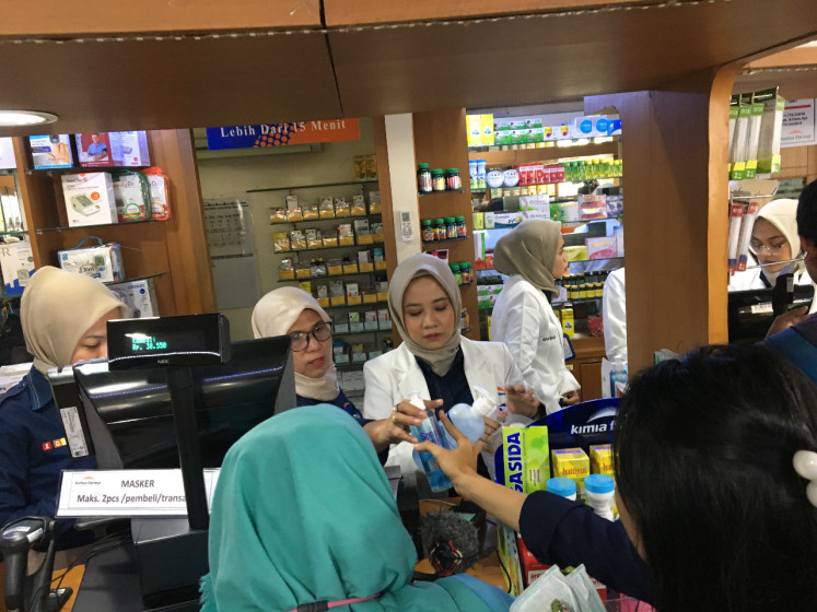 Peope buy masks and antiseptic gel at a Kimia Farma outlet in Menteng, Central Jakarta, on Wendesday, March 4, 2020.