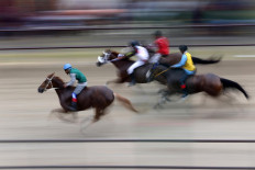In a flash: Jockeys ride at high speed while horse owners and spectators cheer from the stands. JP/Hotli Simanjuntak