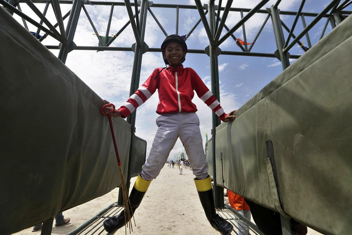 On his mark: Ari, a small jockey, is preparing to ride his horse. This 14-year-old jockey, who started his career last year, is respected by his opponents. JP/Hotli Simanjuntak