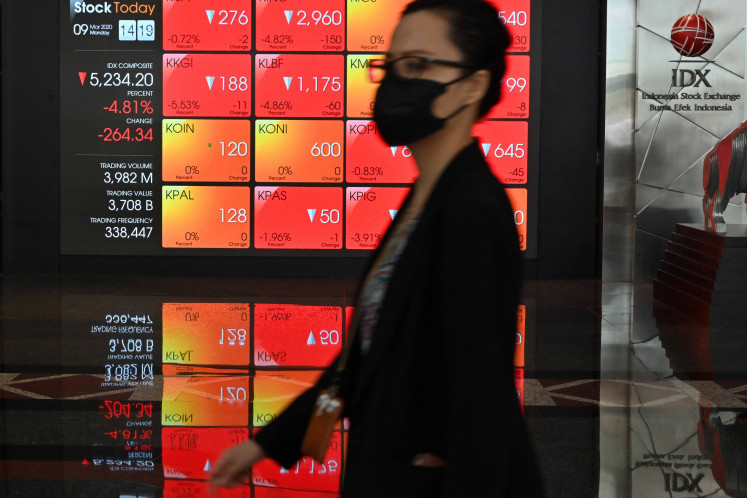 A woman walks past a large screen showing the trading numbers on the Indonesia Stock Exchange (IDX) in Jakarta on March 9, 2020.