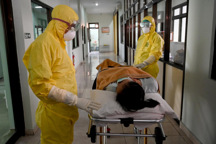 Health workers wearing protective gear take part in an exercise in handling a suspected patient at Sanglah hopital in Denpasar, Indonesia's resort island of Bali, on February 12, 2020.