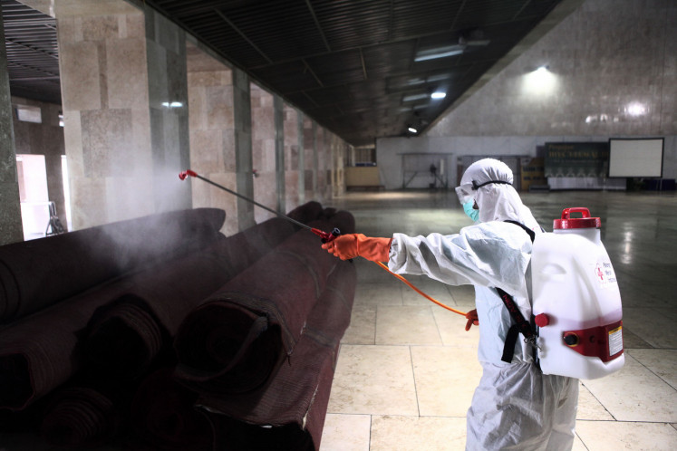 A worker sprays disinfectant in the Istiqlal Mosque in Jakarta, on March 13.
