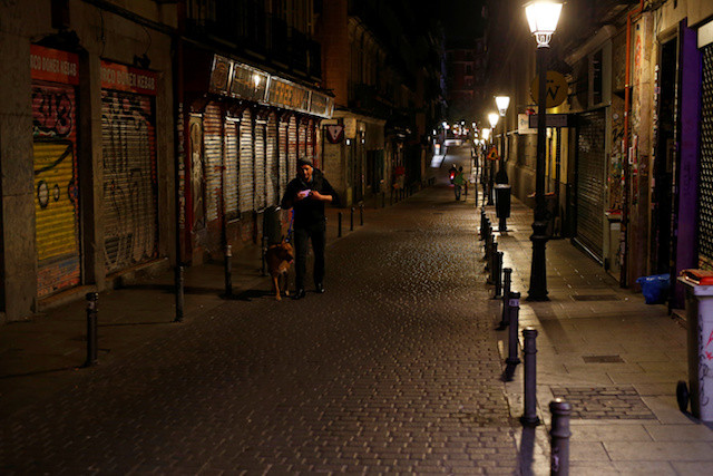 A man walks along an empty street with shuttered shops, as Madrid's internationally famous night life shuts down due to the coronavirus pandemic, in central Madrid, Spain, on Friday.