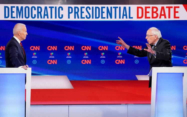 Democratic U.S. presidential candidate and former Vice President Joe Biden listens as Senator Bernie Sanders speaks during the 11th Democratic candidates debate of the 2020 U.S. presidential campaign, held in CNN's Washington studios without an audience because of the global coronavirus pandemic, in Washington, U.S., March 15, 2020.