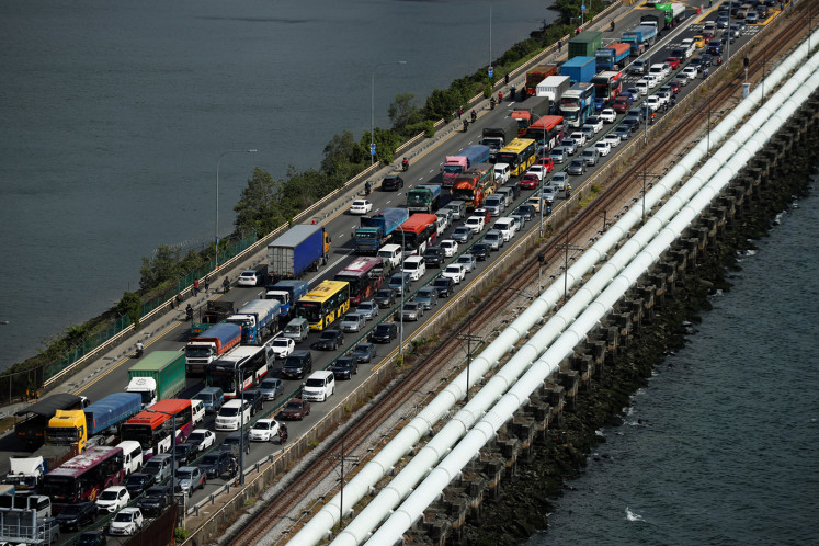 Commuters take the Woodlands Causeway to Singapore from Johor a day before Malaysia imposes a lockdown on travel due to the coronavirus outbreak in Singapore March 17, 2020.