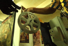Manual loading: Archival staffer Firdaus prepares to mount a film reel in a projector. The film must then be threaded manually through the roller and film gate on the equipment. JP/Xena Olivia