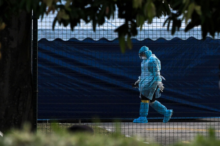 A National Disaster Management Agency (NADMA) officer wearing a hazardous materials suit walks through a health screening area of the Air Disaster Unit (ADA) at Kuala Lumpur International Airport (KLIA) in Sepang, Malaysia, on Tuesday, Feb. 4, 2020.