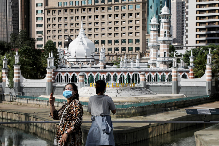 Tourists wearing protective masks take pictures outside a mosque following the outbreak of coronavirus, in Kuala Lumpur, Malaysia March 16, 2020.