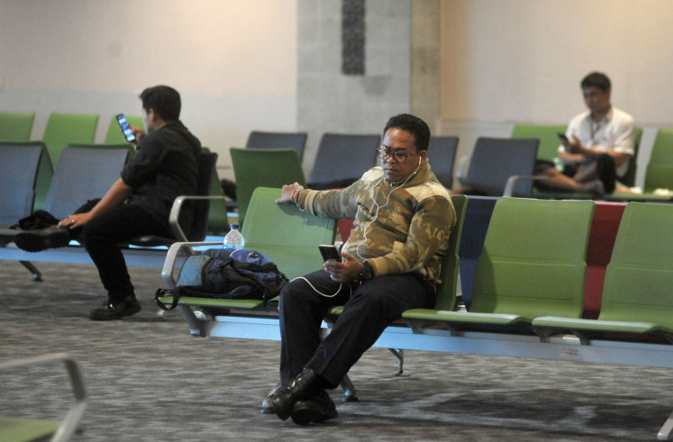 Passengers sit and wait for flight departure schedule at the Domestic Departure Terminal, I Gusti Ngurah Rai International Airport, Bali on March 18, 2020.