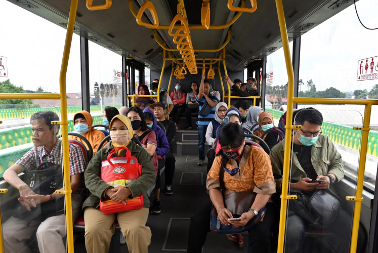 Indonesian passengers wearing face masks ride a Trans Jakarta bus on March 18, 2020.
